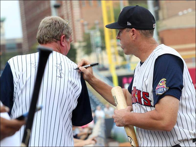 Toledo's Mike Hessman autographs a jersey for a fan before the start of the the game against Louisville.