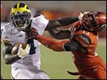 Michigan running back De'Veon Smith (4) is tackled by Utah linebacker Gionni Paul (13).