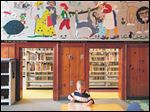 Thomas Gould, 4, plays with a provided toy at the Children's Library, located in the Main Library in downtown Toledo. The library boasts a special room for toddlers and younger children to engage with toys, books, and interactive digital programs. The room, with kid-sized doors, is lined with tiled murals depicting the subjects of classic children's stories.