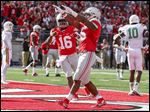 Ohio State's Ezekiel Elliott celebrates scoring one of his three touchdowns as J.T. Barrett congratulates him.