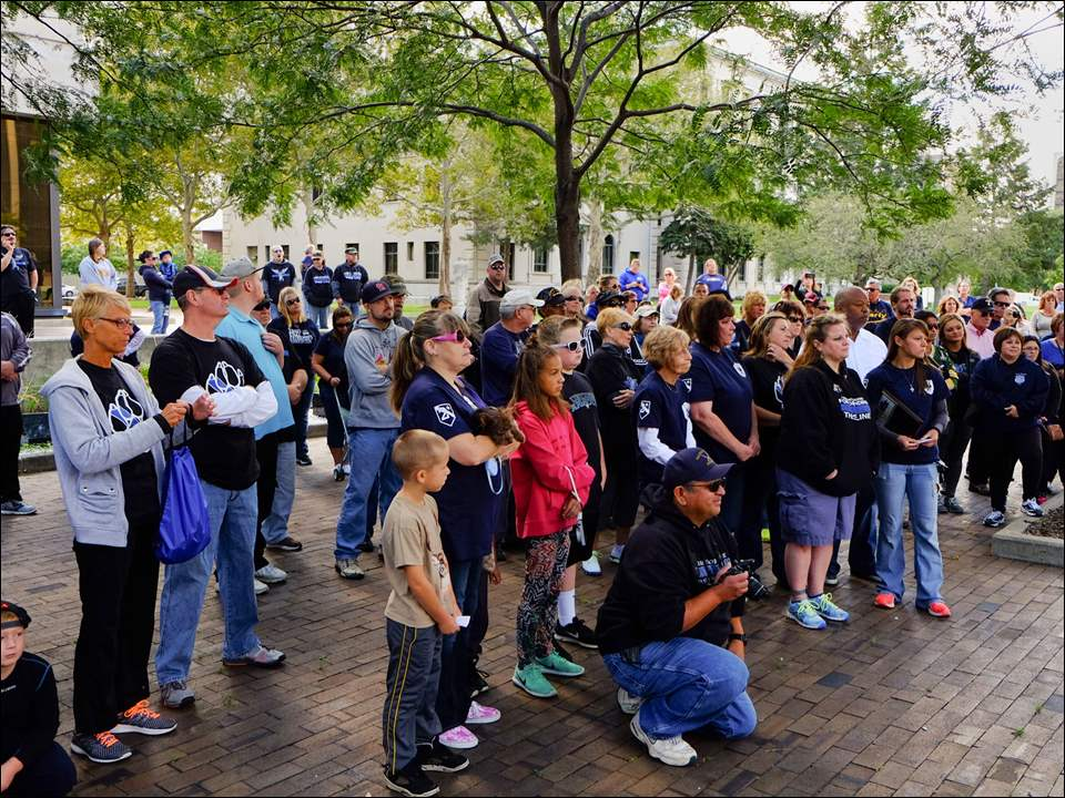 "Marchers listen as TPD chief George Kral thanks them for their support. About 100 people, including the organizers from the group ""Thin Blue Line"" participate in a ""Support Our Police"" walk from the Toledo Police Patrolman's Association to the Toledo Police Memorial Garden in Toledo on Sunday."