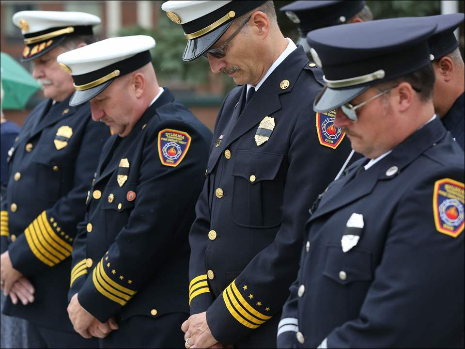 Members of the Sylvania Township Fire Department, including from left, Chief Jeff Kowalski, Deputy Chief Mike Ramm, Deputy Chief Mike Froelich, and Captain Aaron Frye, bow their heads in silence during the September 11 remembrance ceremony in River Centre Park in Sylvania, Friday, September 11, 2015.  The Blade/Dave Zapotosky