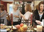 Dana Anderson of Greeley, Colo., center left, and Marcie Jacobs of Kidron, Ohio, center right, join other women for the August meeting of the group Dining for Women at the home of Donna and Bob Mens in Sylvania.