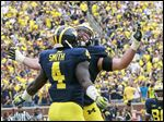 De'Veon Smith, left, and Erik Magnuson were a big part of the Wolverines' dominating ground attack on Saturday.