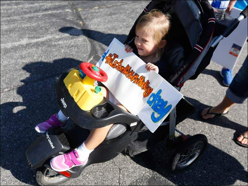 Lyla Adkins, 4, holds a sign in the parking lot before a Washington Local Schools special school board meeting at the Administration Building in Toledo.  Her siblings go to the schools.