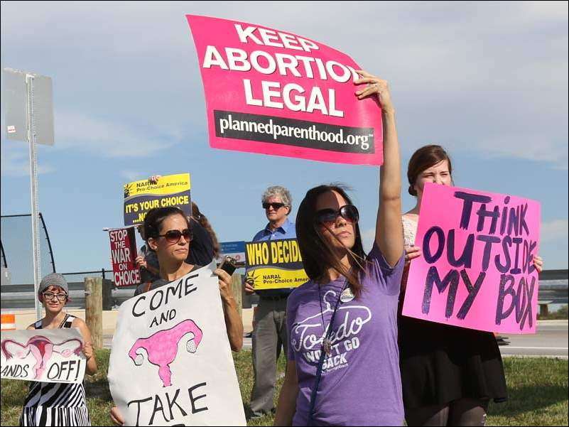 From left, Chloey Wilburn, Jaclyn Hady, Toledo Mayoral candidate Mike Ferner, Kristin Hady, and Airen Meyer, hold signs proclaiming their support for legal abortion during the Wednesday rally.