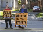 Toledo mayoral candidate Mike Ferner, joined by supporter Sean Nestor, takes his campaign for more street repair funding onto Collingwood Boulevard.