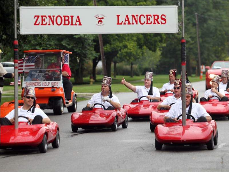 The Zenobia Lancers drive their red cars in the Shriner's Parade in downtown Perrysburg.
