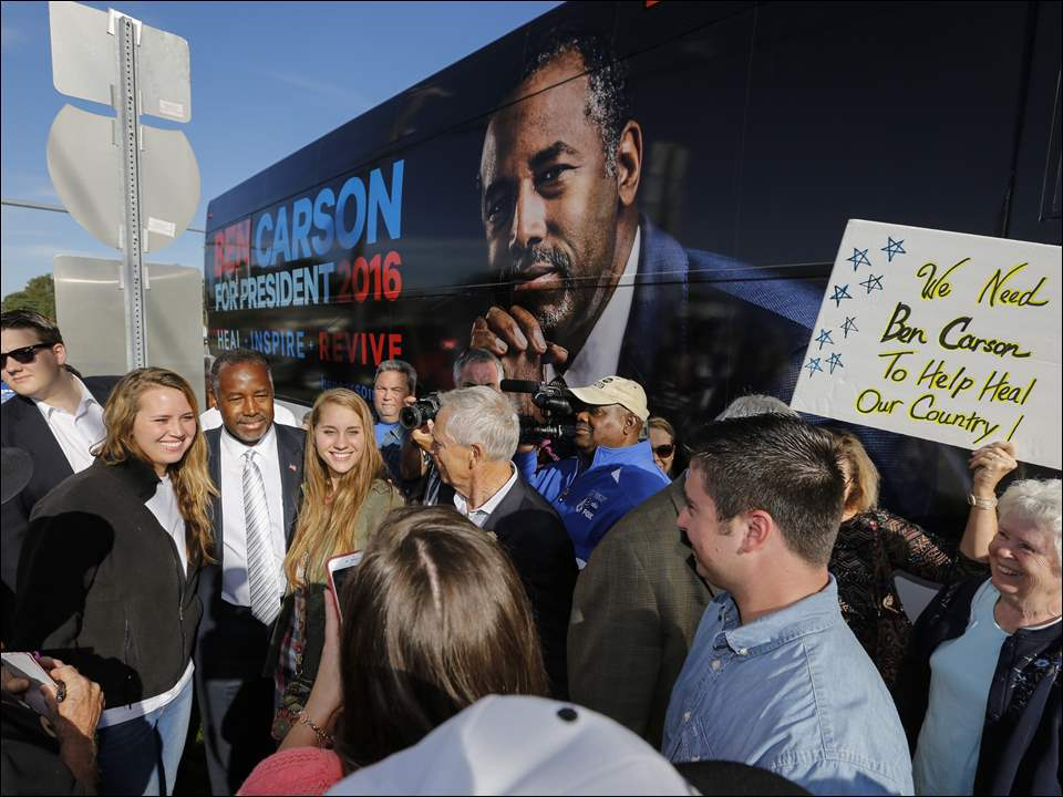 Presidential candidate Dr. Ben Carson poses for a photo with sisters Audrey Barger, left, and Tess Barger, as he greets a large crowd.