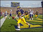 Michigan quarterback Jake Rudock scores on the first of his two touchdown runs against BYU on Saturday afternoon.