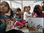 Aaliyah Zavala of Bloomdale, Ohio, left, Sandra Avila of Woodville, and Yakelin Gonzalez of Pemberville clutch their books as they listen to a story.