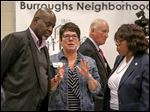 Toledo mayoral candidates Mike Bell and Paula Hicks-Hudson, right, listen as Mar-cia Weisen-burger explains how the forum will run before it gets under way Monday at Burroughs Elementary School in South Toledo. Behind them is candidate Car-ty Finkbeiner.