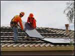 Electricians  Steven Gabert, left, and Adam Hall  install solar panels on a roof for Arizona Public Service company in Goodyear, Ariz. Traditional power companies compete for rooftop space for small-scale solar energy.