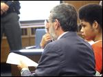 Attorney Paul Geller consults with his client, Devonte Brown, 16, during the teen's arraignment. The teen was certified to stand trial as an adult in the stabbing deaths of his estranged girlfriend and her brother and the nonfatal stabbing of their mother on Aug. 10. His trial is set for November.