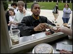 University of Toledo graduate student Loren Branch buys lunch at the Displaced Chef food truck at the University of Toledo as part of homecoming festivities.