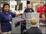 Nancy Hall, project manager for NASA's HUNCH program at Glenn Research Center, speaks to Bedford High School students at the school's machining and welding shop about the parts of a box that they will build for the International Space Station. The boxes are for storing food, astronauts' personal items, and materials for experiments.