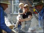 Jennie Kummerer, holds her son Keenan Heintschel, 3, of Perrysburg, watch while Bob Bailey, left, and Gary Miller, right, can apple butter during the annual Grand Rapids Apple Butter Festival on October 10, 2015.
