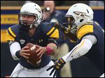 Toledo's quarterback Phillip Ely (12) fakes a handoff to Kareem Hunt (3) during the third quarter of the win vs. Eastern Michigan on Saturday.