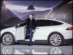 In this file photo, Elon Musk, CEO of Tesla Motors Inc., introduces the Model X car at the company's headquarters in Fremont, Calif.
