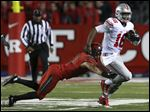 Ohio State quarterback J.T. Barrett (16) breaks a tackle by Rutgers defensive back Anthony Cioffi (31).