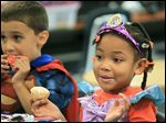 Alexander Kamelesky and D'Asia Scott, both 5, eat snacks after Birmingham Elementary School's Halloween parade for kindergarten to fourth-grade students.