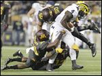 Michigan running back De'Veon Smith is tackled by Minnesota's Eric Murray, left, and Jack Lynn.