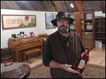 Will Ouweleen, owner of Eagle Crest and O-Neh-Da wineries, poses with a bottle of