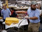 Jeff Wilson, left, and David Kraft wheel hunks of cheese to be sliced for sale during the holiday cheese slicing event at The Andersons General Store in West Toledo Saturday.