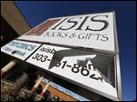 A panel of the sign outside Isis Books and Gifts store is broken today in Englewood, Colo.