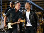 Bruce Springsteen, left, and John Legend perform at Shining a Light: A Concert for Progress on Race in America at the Shrine Auditorium in Los Angeles.