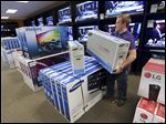 Dalton Schardt arranges a display of televisions at the Appliance Center in Maumee. Store officials say they expect electronics to sell well over the holidays and are confident about their inventory.