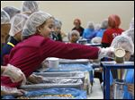 Wayne Trail Elementary student Caitlin Smalley helps pack meal kits for hungry children in Africa as part of the Feed My Starving Children organization. The goal was to pack 225,000 meals during the two-day event, which ends today.