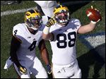Michigan tight end Jake Butt, right, celebrates his touchdown catch with teammate De'Veon Smith during the first half of the Wolverines' victory over Penn State.