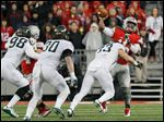 Ohio State quarterback J.T. Barrett is rushed by Michigan State LB Jon Reschke.