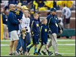 Former Michigan coach Lloyd Carr, far right, leads his grandsons T.J. and Tommy Carr, daughter-in-law Tammi Carr, and son Jason Carr, far left, holding his son Chad Carr, onto the Michigan Stadium field in September.