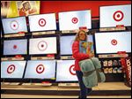 A customer walks past a bank of flat screen televisions at a Target store in South Portland, Maine.