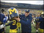 Jon Falk, who retired last season after 40 years as Michigan's head equipment manager, holds the Little Brown Jug following the Wolverines' win on Oct. 5, 2013.