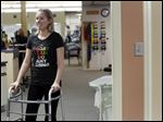 Traci Muszynski uses a walker while at physical therapy at the Wildwood Athletic Club.