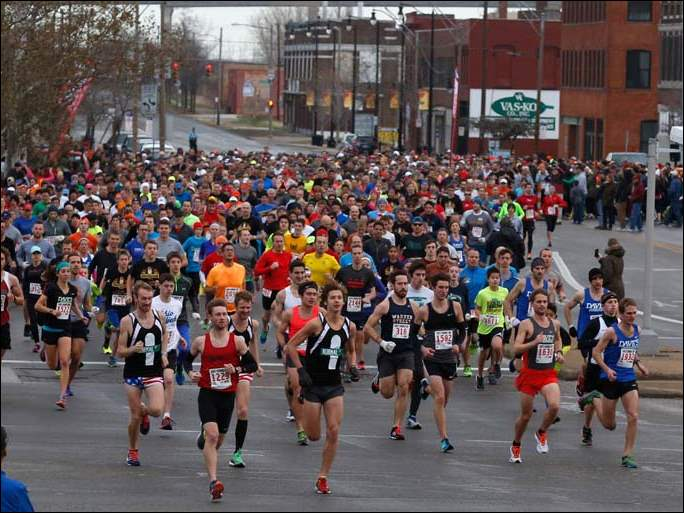Runners cross Cherry St. as they down Summit St. during Dave's Turkey Chase 5K run in Toledo.