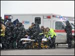Emergency personnel transport an officer to an ambulance after reports of a shooting near the Planned Parenthood clinic in Colorado Springs, Colo.