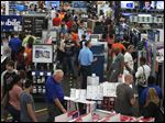 People look at merchandise while holiday shopping at Best Buy on Thursday in Panama City, Fla.