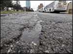Part of eastbound Jackson Street in downtown Toledo still has large cracks in the pavement.
