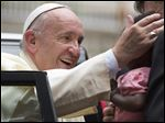 Pope Francis reaches out to kiss a baby carried by an aide from the crowd, after leading a Holy Mass for the Martyrs of Uganda at the area of the Catholic Sanctuary in the Namugongo area of Kampala, Uganda Saturday, Nov. 28, 2015. Pope Francis is in Uganda on his first-ever trip to Africa, a six-day pilgrimage that has already taken him to Kenya and then onwards to the Central African Republic. (AP Photo/Ben Curtis)
