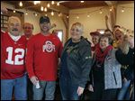 Newlyweds Jeff and Lynn Gajdostik, center, celebrate their wedding flanked by friends Jerry Thomas, an Ohio State fan at left, and Susan Jagielski, a Michigan fan at right.