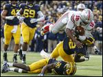 Ohio State's J.T. Barrett dives over Michigan players Jarrod Wilson (22) and Jourdan Lewis (26) for a touchdown in the third quarter Saturday.