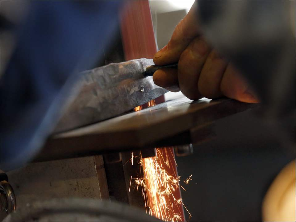 Butch Sheely grinds a Bowie knife in his shop in Grand Rapids.