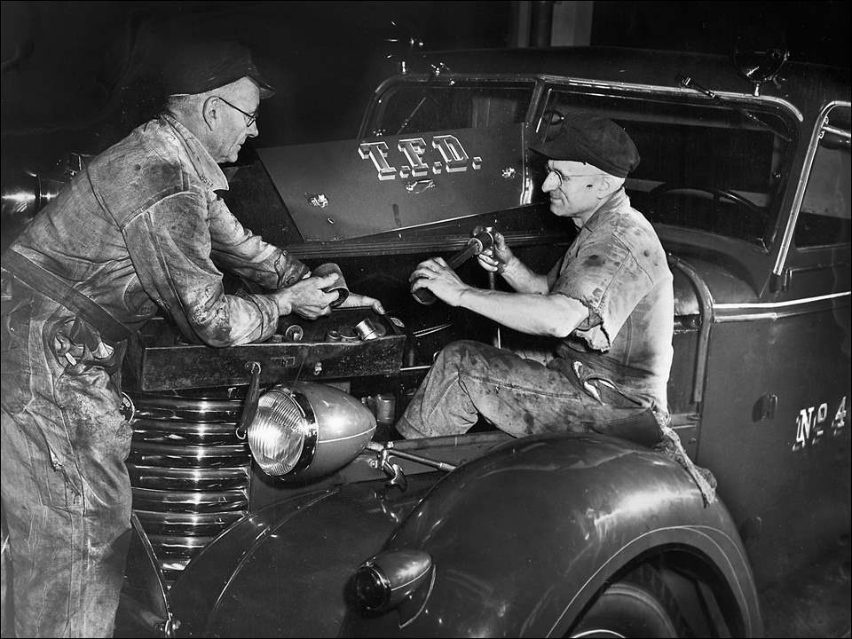 """Keeping city vehicles road ready""    In this Toledo Times photo, taken Sept. 24, 1945, Toledoans Andrew Molnar and Louis Glanzman were working on a motor overhaul, selecting a socket wrench for a motor head. The two mechanics were tasked with keeping the fire division vehicle in shape to respond to the next alarm."