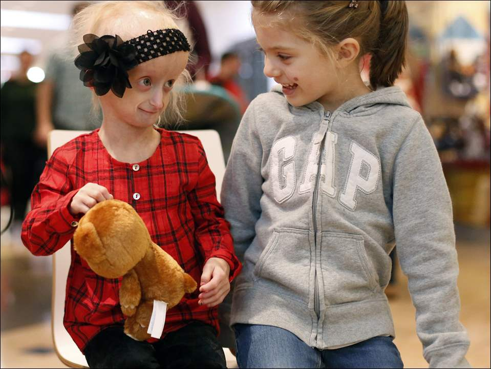 Carly Kudzia, left, and Kaya Perry, 4, right, of Sylvania, sit together in front of the FoodieCards kiosk during holiday shopping Saturday.