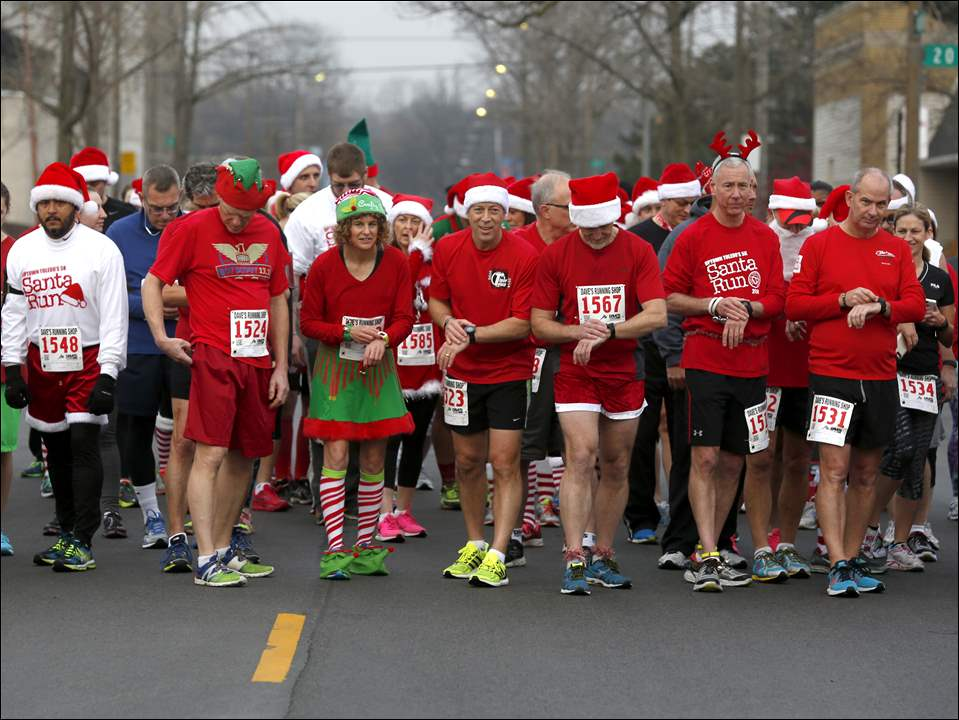 Runners prepare to start their stopwatches at the start of the race on Madison Ave. during the Uptown 5K Santa Run in Toledo.