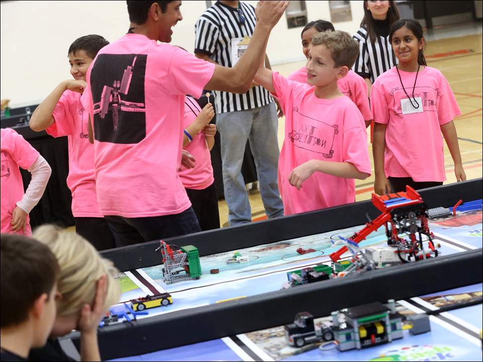 Nxt Revolution parent volunteer Prak Naik, center, high fives Andrei Radjenovic, 10, after their team's robot preformed well during the First Lego League STEM Center Ohio Regional tournament Saturday, Dec. 12, 2015, at Sylvania Southview High School.